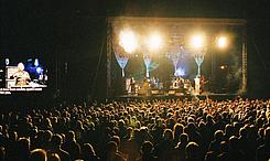 Bühne mit Band und Gebärdensprachedolmetscherin, übertragen auf Großleinwand links